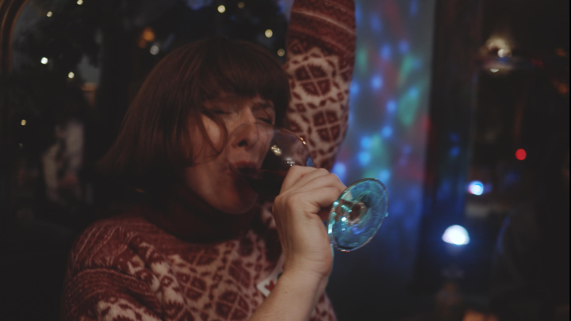 A woman drinking at the City Night's Office Christmas Party